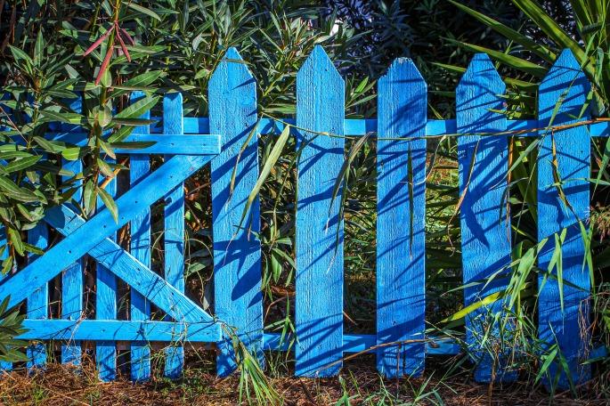 Das Bild zeigt einen blauen Lattenzaun