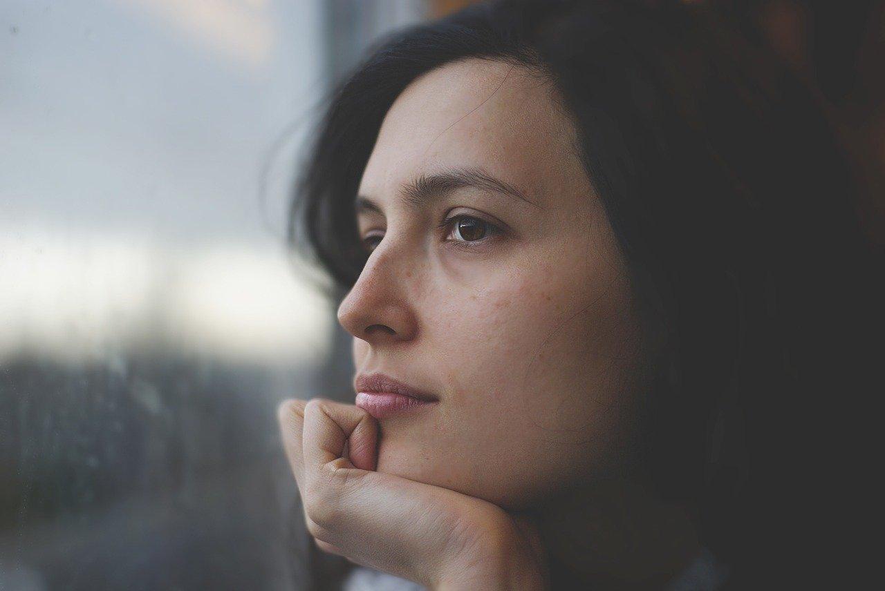 Das Bild zeigt eine nachdenkliche junge Frau.