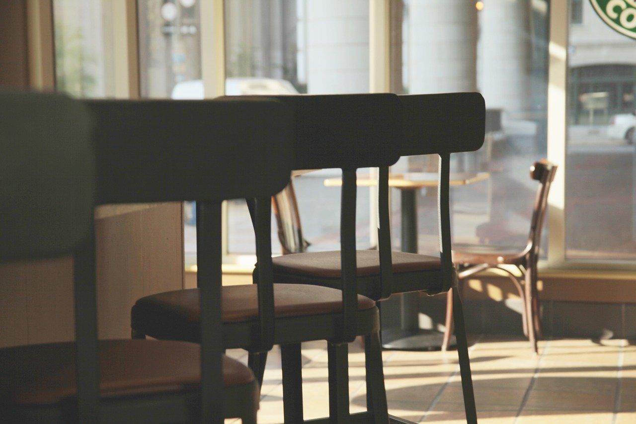 Das Bild zeigt leere Stühle in einem Café.