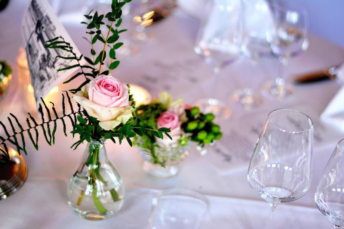 Das Bild zeigt einen festlich gedeckten Tisch mit einer Rose.